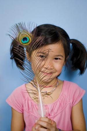 Girl looking at iridescent peacock feather with nanoscale color