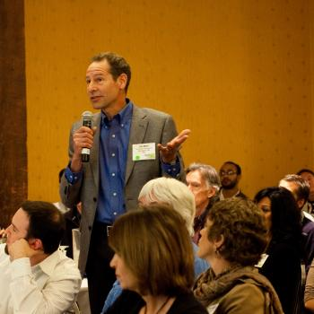 Man standing with microphone in a group forum discussing STEM topics societal implications
