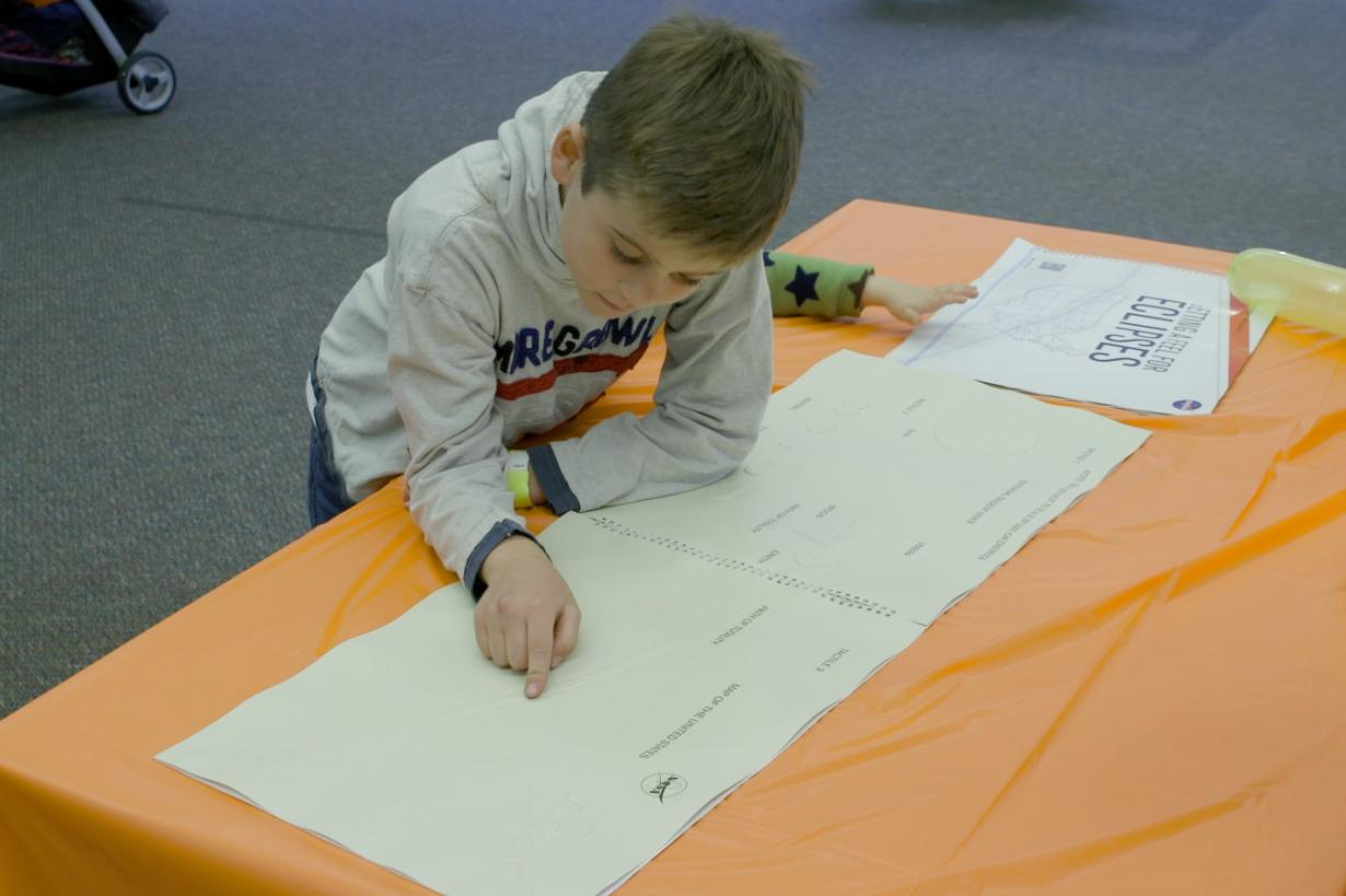 "Child using the Braille book, called ""Getting a Feel for Eclipses,"" features graphics that teach users about the interaction and alignment of the sun with the moon and Earth"