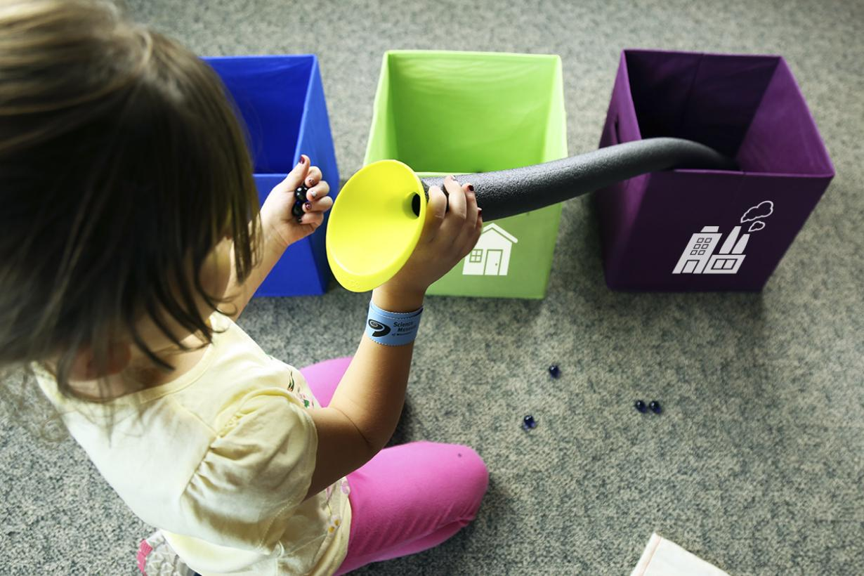 Child using putting marbles into tube with funnel in Water Roll SustainABLE kit activity