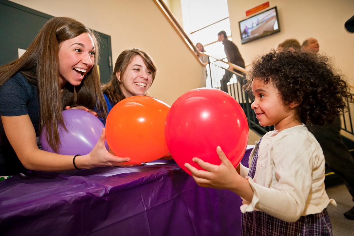 Learner smells balloons with educators