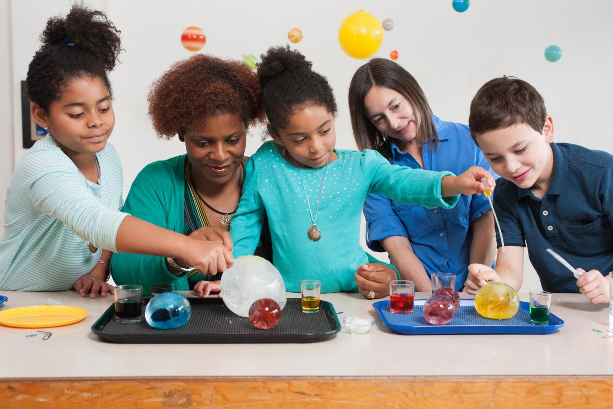 Children and adult investigating globes of ice in  Icy Orbs activity