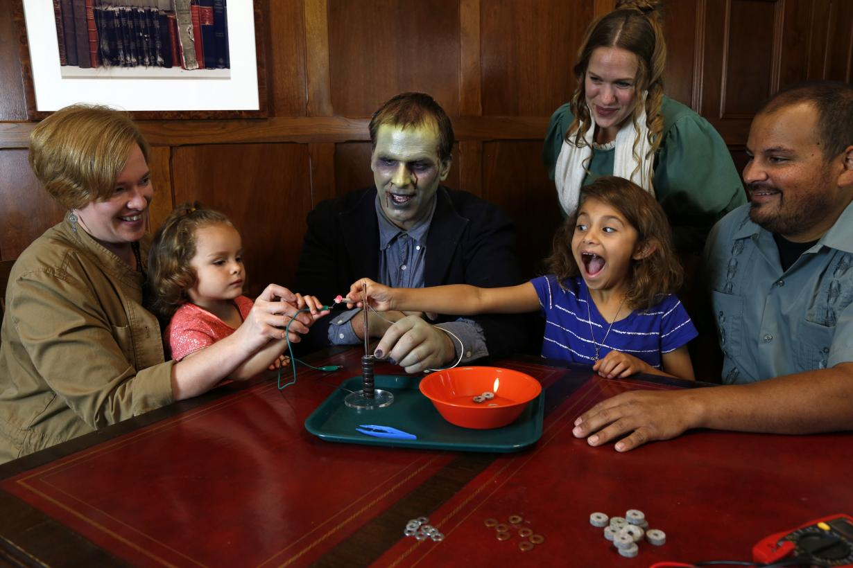 Children with surprised faces and adults using the Frankenstein kit Battery Stack activity  - adults dressed as Mary Shelley and the Monster