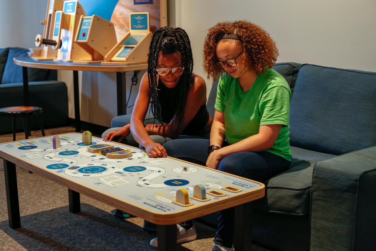 Girls playing space game in Sun Earth Universe exhibition
