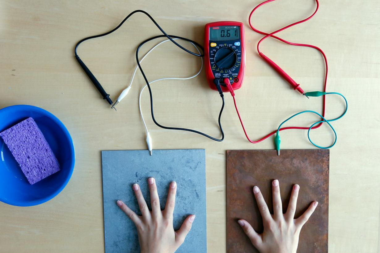 Participant's hands touching the steel and copper plates, connected to a multimeter