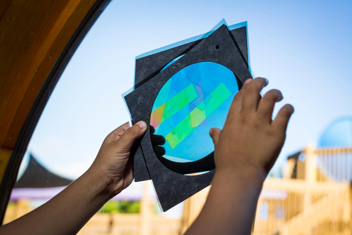 Polarized Light activity with hands holding paper and polarizing tape materials up to the window