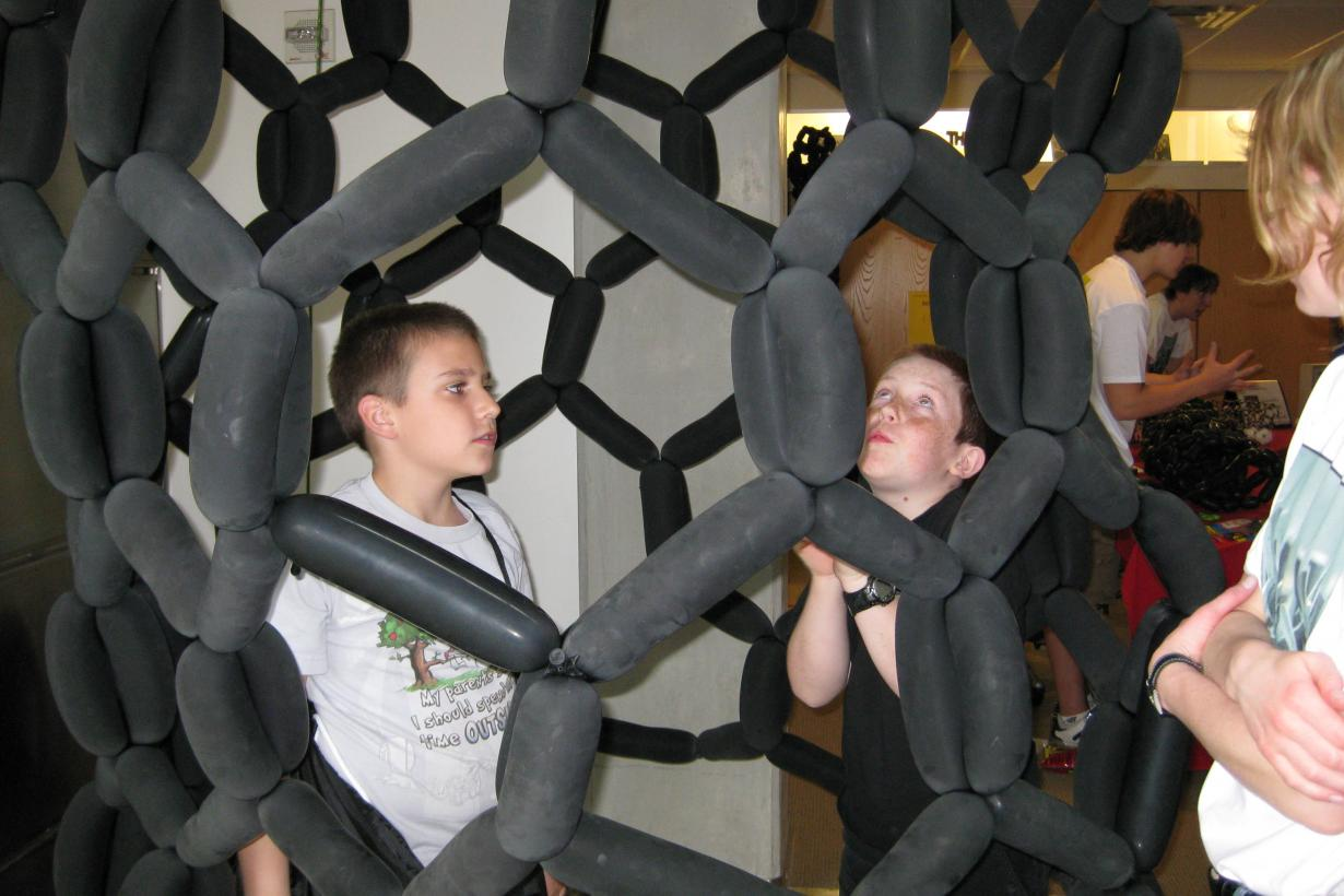 A person inside of a balloon model of a carbon nanotube.