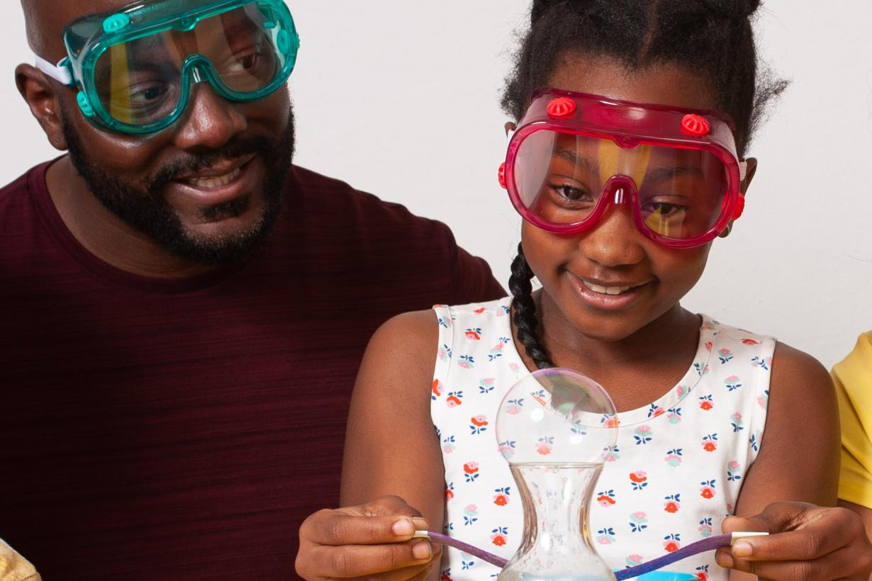 Father and daughter observing bubble in Sublimation Bubble activity in Explore Science: Let's Do Chemistry kit