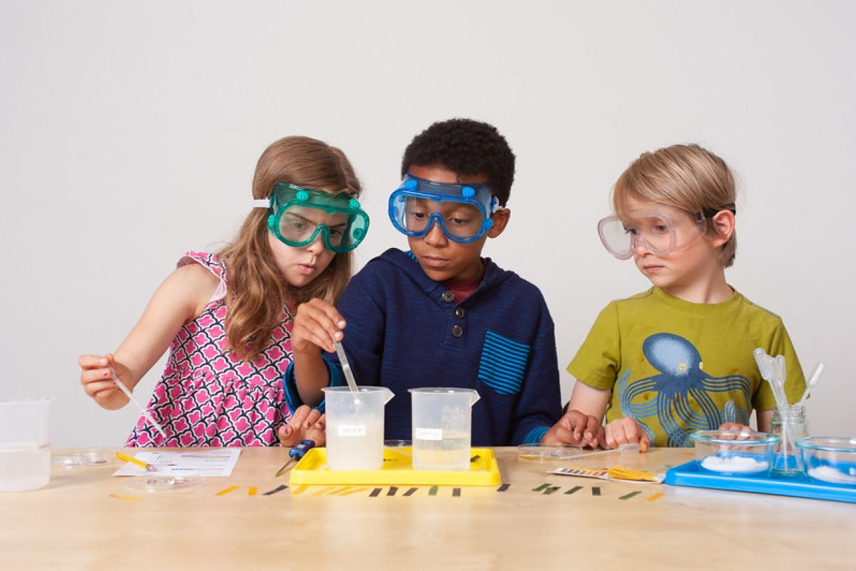 Three children measuring and mixing liquids using Explore Science: Let's Do Chemistry activity