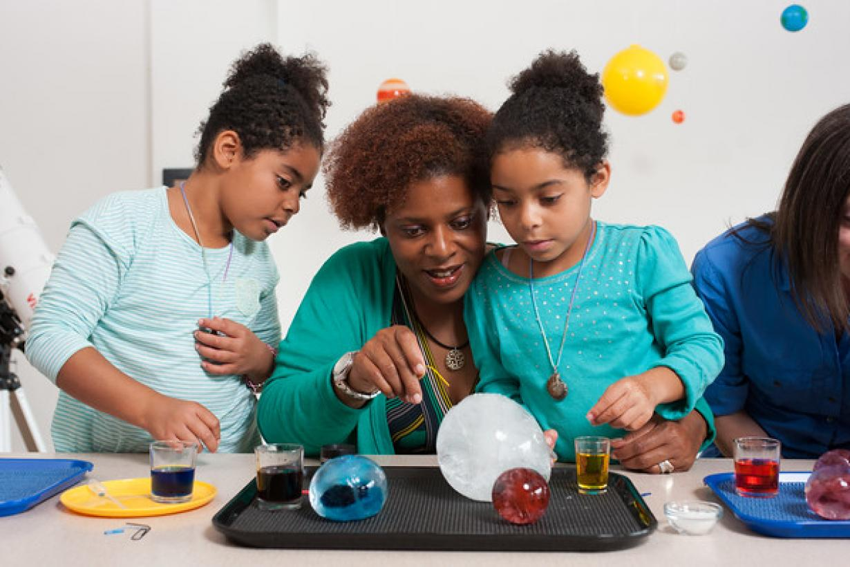 Mother and two daughters investigating giant balls of ice in Ice Orbs activity