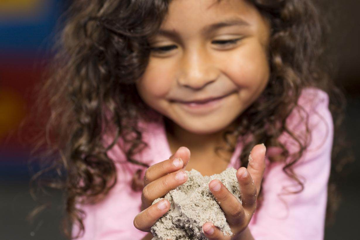 Girl holding sand in hands