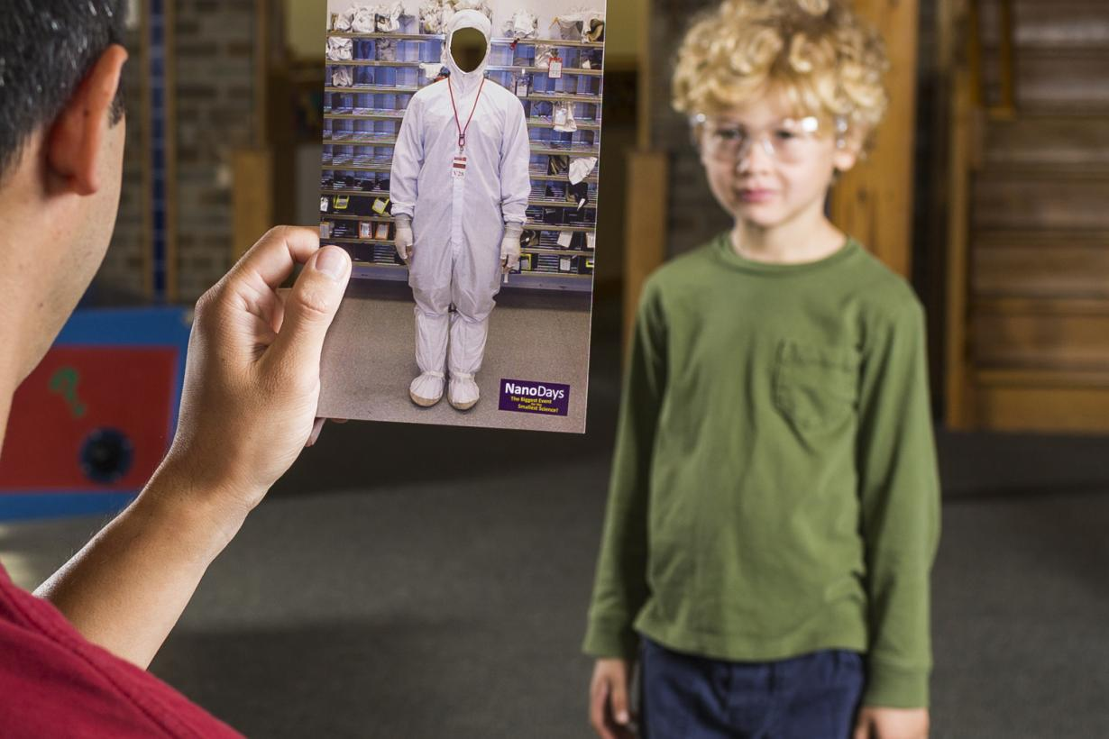 Parent holding card to simulate child dressed as a nonscientist in Dress up like a Nanoscientist NanoDays activity