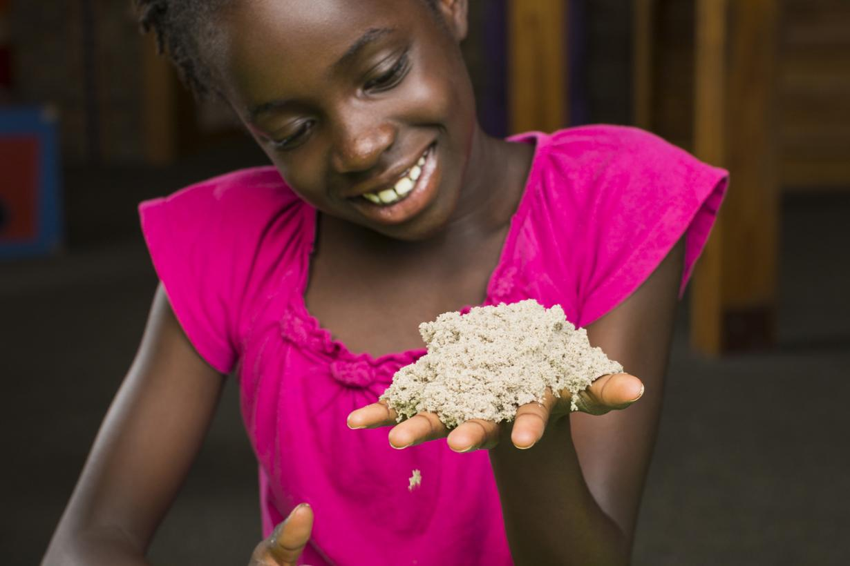 A girl plays with special sand.