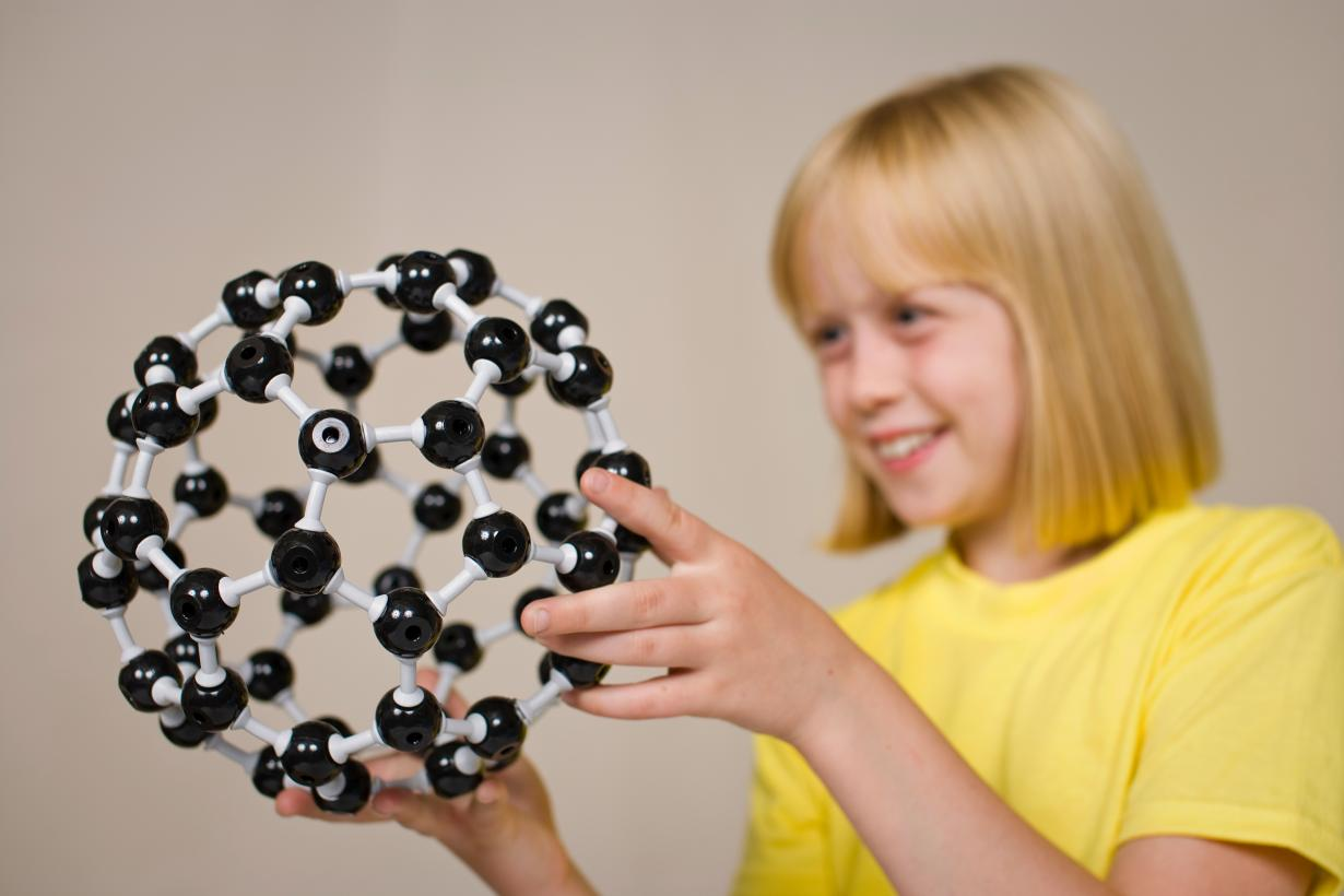 A girl looking at a model of a buckyball