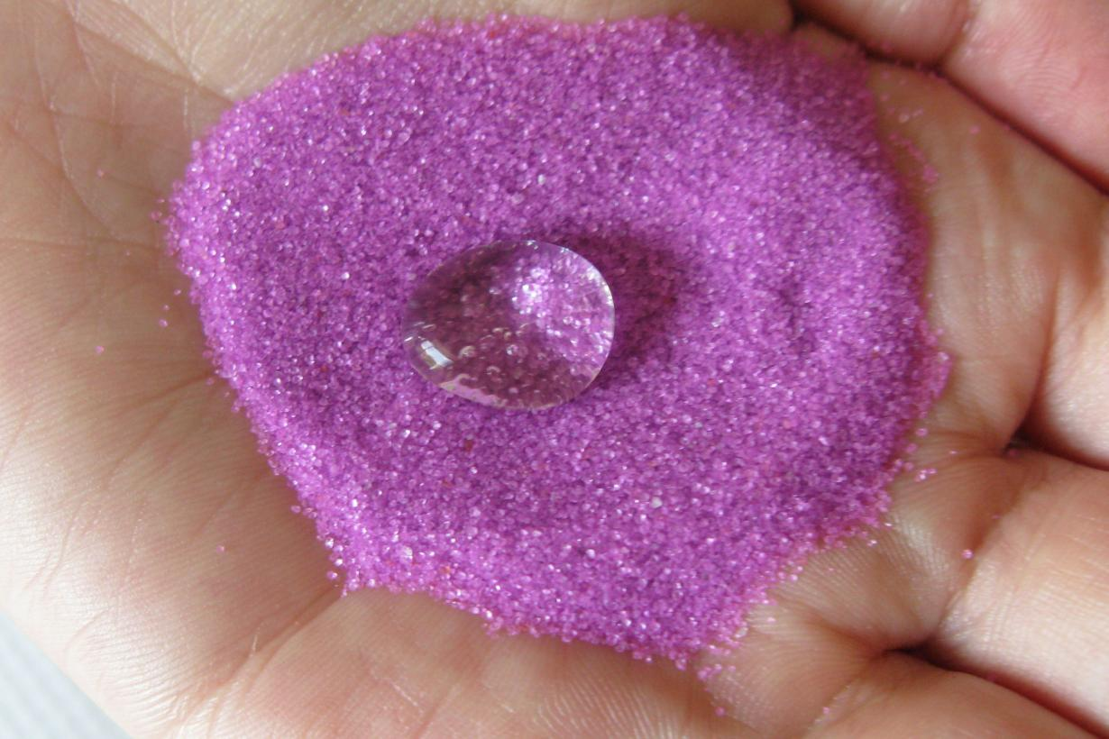 Exploring Products - Nano Sand's pink superhydrophobic sand.  A person is holding some pink sand with a big drop of water on top.