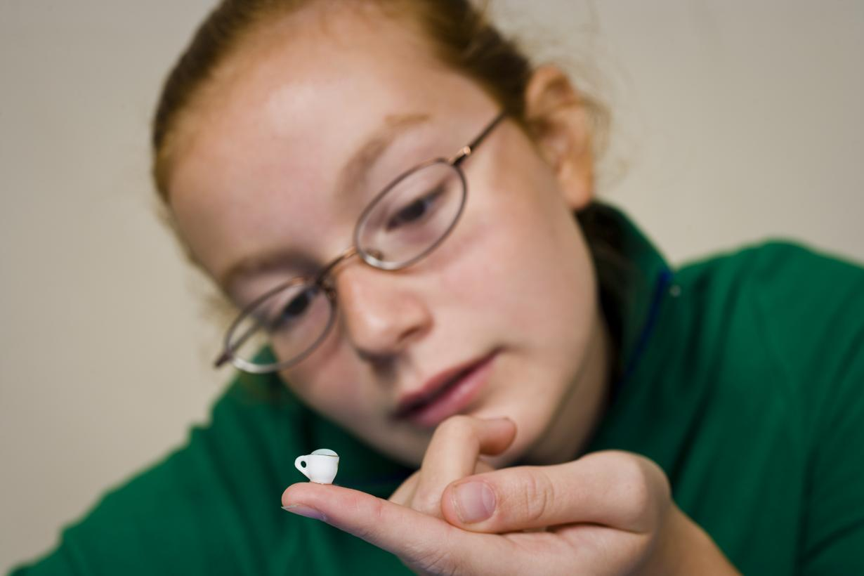 A person looking at a very very small teacup on the tip of their finger.