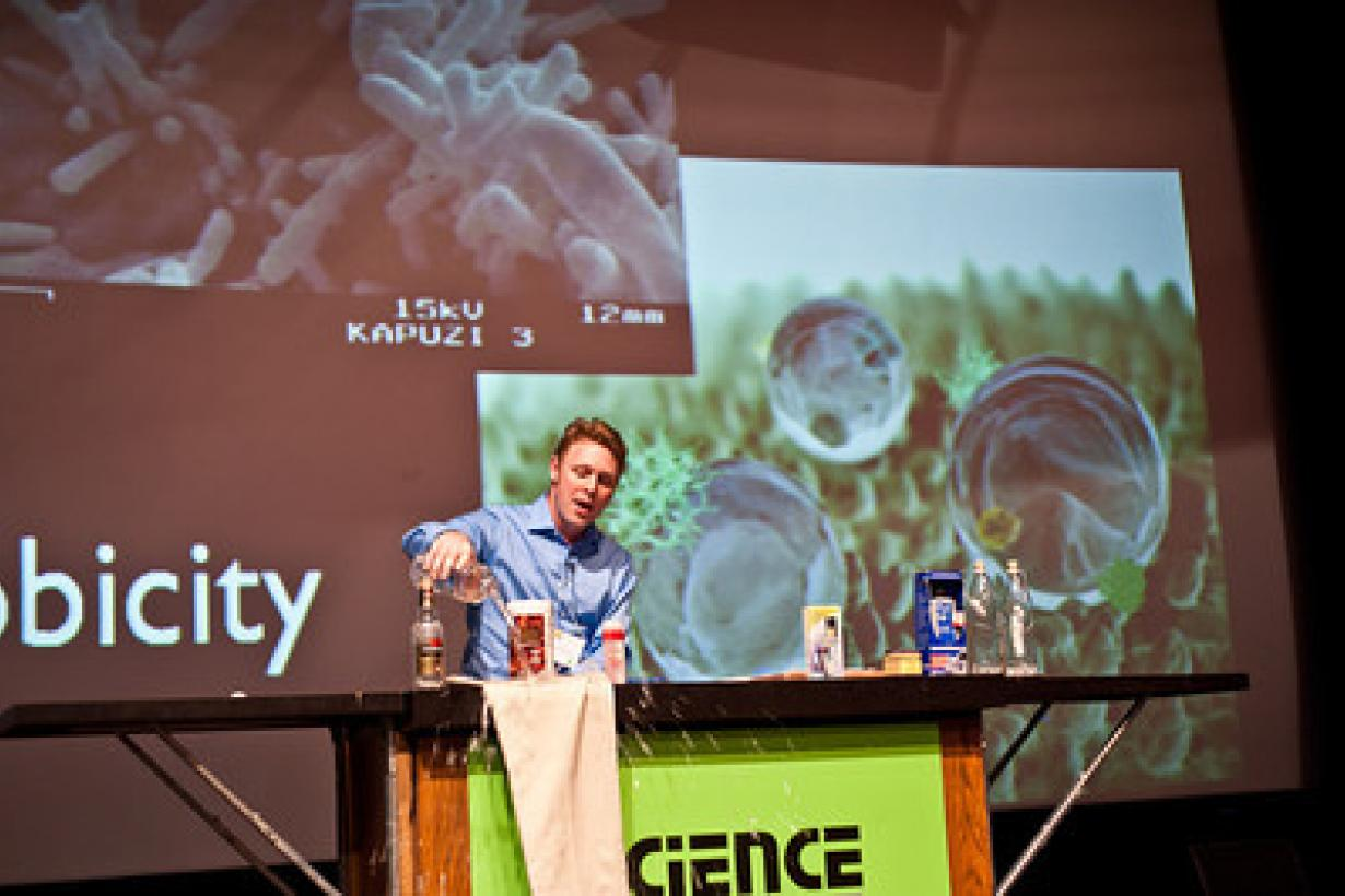 Educator on stage showing nano pants hydrophobic properties