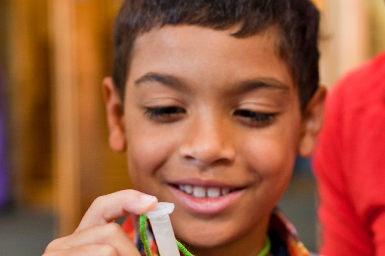 Boy holding small plastic test tube