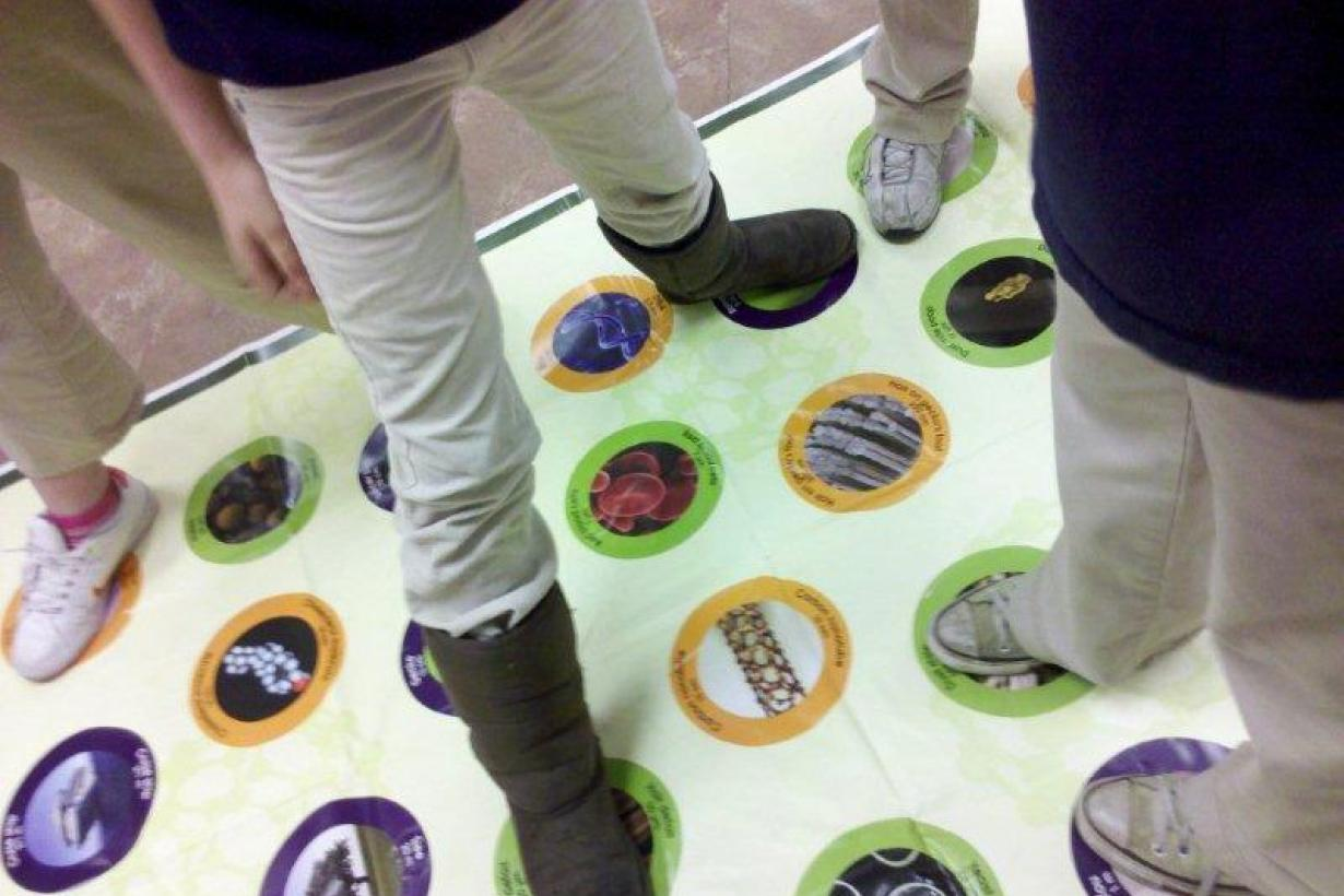 People playing Stretch-ability, a hand and foot game, on a mat.