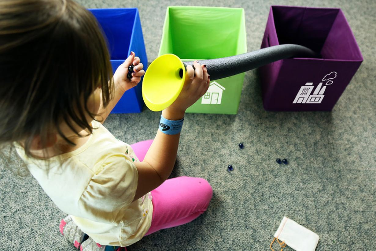Child using tube in water roll SustainABLE activity