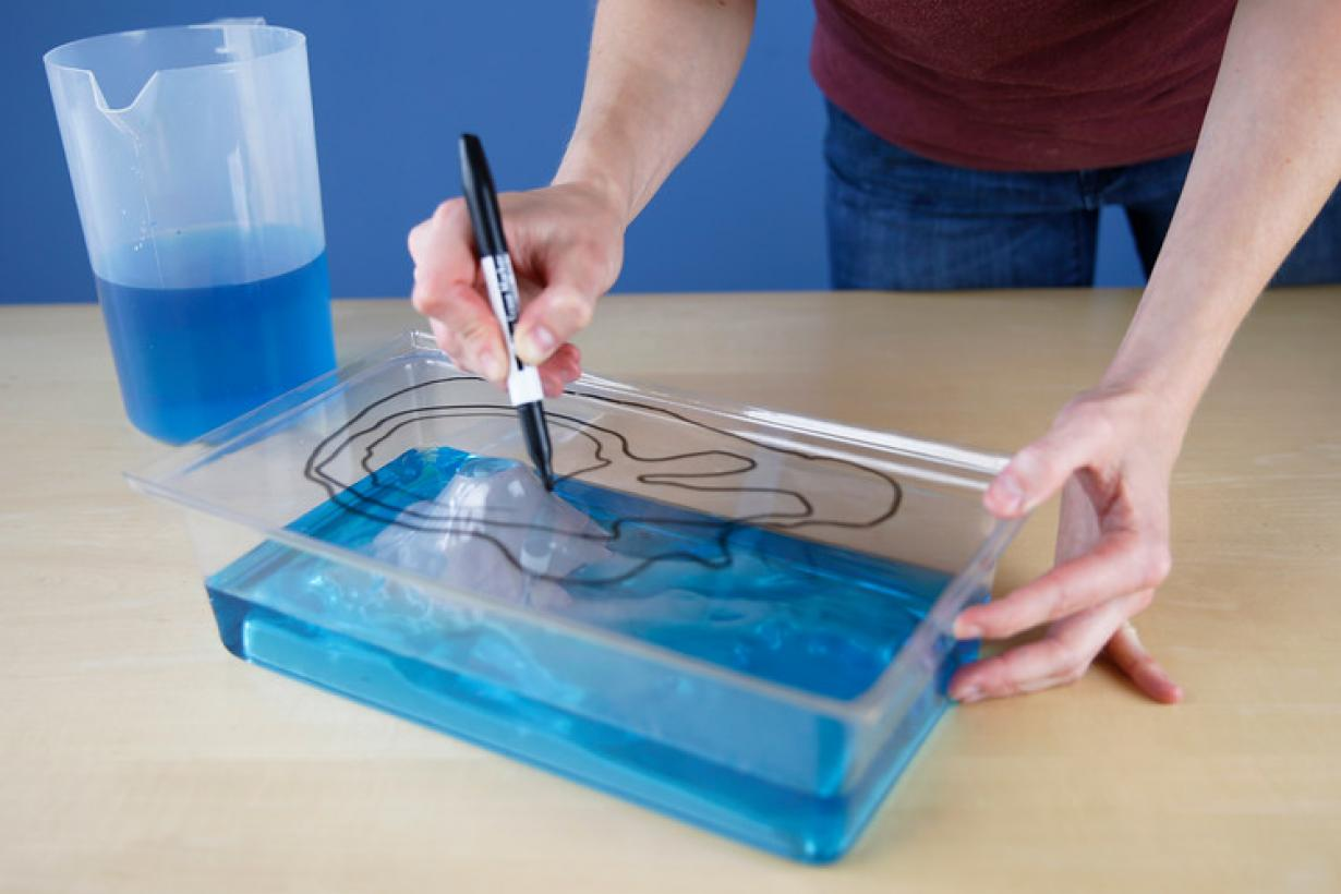 Exploring Earth: Rising Sea activity showing hands drawing contour lines on plastic box