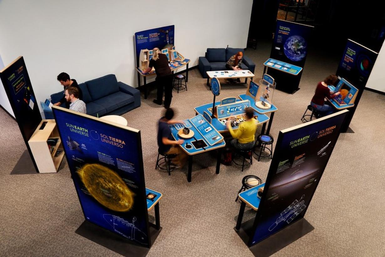 Sun, Earth, Universe exhibition Birdseye view of visitors interacting with exhibits