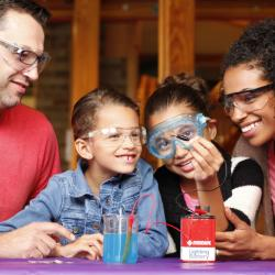 Parents and two children using Exploring Fabrication - Electroplating (NanoDays 2014)