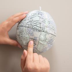 Fingers pointing to globe model of the Moon