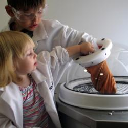 Little boy and girl looking using glove in an alcove in the NanoLab exhibit