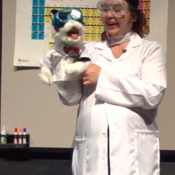 chemistry training video screenshot with presenter and chemistry cat puppet