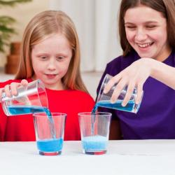 Girls pouring liquid into cups using DIY Nano Fizz activity