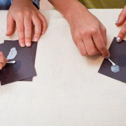 Hands using cotton swabs spreading sunblock on black paper using DIY Nano sunblock activity