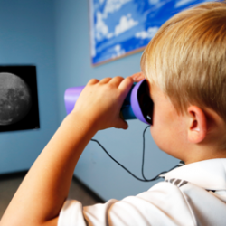 Child using binoculars to look at an enlarged photo of the Moon in Hide and Seek Moon activity