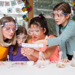 Children and and adult examining color changes in Explore Science: Let's Do Chemistry activity