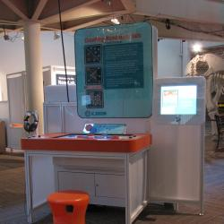 Creating Nanomaterials exhibit as viewed from the right with a stool placed in front of it.