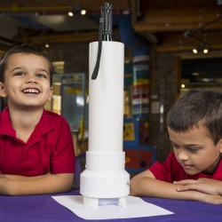 Two kids using a model Transmission Electron Microscope