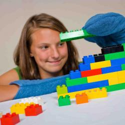 A person building a structure with Lego® while wearing mitts.