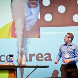 Educator on stage with aerosols coming out of bottle
