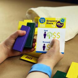 Hands holding blocks and cards for Future Builder SustainABLE activity