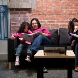 two mothers and children sitting on a couch reading Nano books in the Nano exhibition