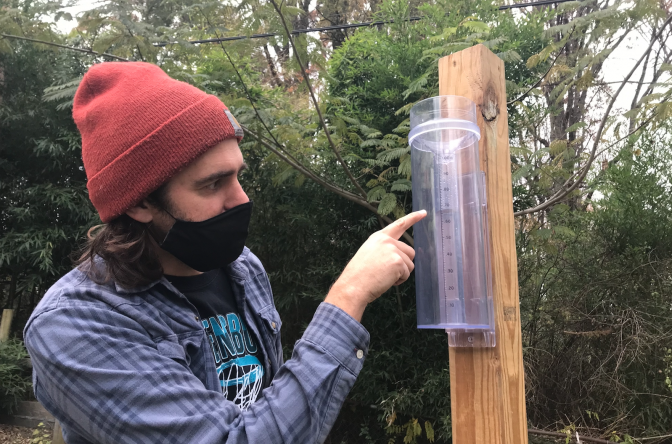Citizen scientist taking a precipitation measurement on a CoCoRaHS rain gauge
